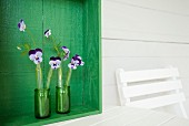 Upcycling: glass vanilla pod tubes used as DIY vases for violas