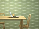 Laptop & mobile phone on wooden table in front of green and white polka-dot wallpaper