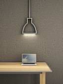 Laptop on wooden table below modern neon lamp against grey concrete wall
