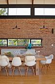 Essplatz mit Klassikerstühlen um Massivholztisch oberhalb Designerleuchten, gegenüber Ziegelwand mit Oberlichtern in modernem Wohnraum