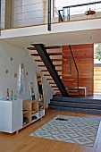 Patterned rug on wooden floor in front of platform and staircase running up wall to one side