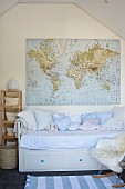 Pale blue cushions on child's bed with integrated drawers below world map hung on gable-end wall of attic room