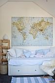 Hellblaue Kissen auf Kinderbett mit integrierten Schubladen an Giebelwand mit aufgehängter Weltkarte im Dachzimmer