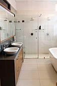 Designer bathroom with twin sinks, mirrored wall cabinet and two rainfall showers behind glass partition