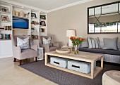 Comfortable living room with white fitted shelving, beige armchairs, wicker sofa and floor cushions on lower shelf of coffee table