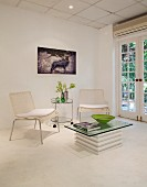 Bright lounge area with wicker chairs, serving trolley and glass table