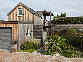 Weathered wooden house with attached garage, screen fence and flowering aloe next to entrance