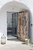 Rustic wooden front door and modern glass door in arched doorway of stone house