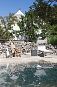 Sun loungers in front of stone wall next to pool outside trullo