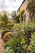 Blühender Garten mit Rankstab und formgeschnittenem Buchs vor Herrenhaus