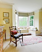 Antique armchair next to window bay with masonry window seat in yellow-painted living room