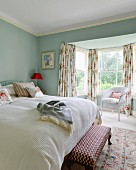 Upholstered footstool next to double bed in front of white wicker chair in window bay in bedroom painted light blue