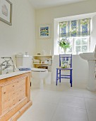White tiled floor, bathtub with wooden surround and chair below lattice window in rustic bathroom