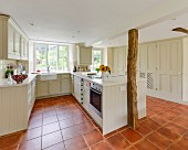 Open-plan country-house kitchen with rustic wooden columns, pale cupboards and terracotta floor tiles
