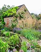 Garten mit Gartenteich vor rustikalem Haus aus Naturstein