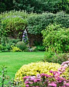 Flowering shrubs, clematis climbing through obelisk, lawn and wall in well-tended garden