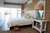 Bedroom with white fitted wardrobe, turquoise table lamp, scatter cushions on bed and brown wallpaper