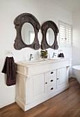 Weißer Waschbeckenschrank mit rustikal verzierten Holzrahmenspiegeln in Landhausambiente