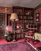 Herrschaftliche Bibliotheksecke mit Stehleuchte, Lesesessel mit Samtbezug vor Bücherregal