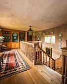 Möblierte Galerie mit Holzbalustrade um offenem Treppenraum, im Hintergrund Einbauschrank aus Massivholz mit Regalelementen