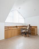 Modernes Büro unter dem Dach mit großem Schreibtisch