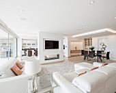 Luxuriöser offener Wohnraum, mit weißen Sofas und modernem Essplatz