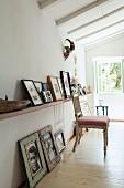 Antiker Polsterstuhl vor Wand mit Ablage, darauf und darunter gerahmte angelehnte Bilder