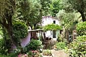 Sommerlicher Garten mit verstecktem Gartenhäuschen und berankter Pergola, im Hintergrund Landhaus