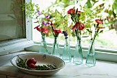 Rosemary sprig in bowl and flowers arranged in small bottles on windowsill