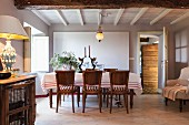 Tablecloth on dining table and wooden chairs in Mediterranean dining room with white, wood-beamed ceiling