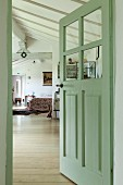 Half-open interior door painted pastel green with view into sleeping area in open-plan converted attic