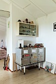 Upcycled sideboard in corner below collection of lighters in wall-mounted cabinet