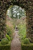 View through archway in hedge into topiary garden