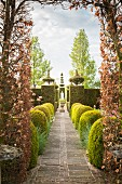 Garden path lined by geometrically clipped bushes and topiary