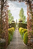 Von geometrischen und figürlichen Formschnittgehölzen begrenzter Gartenweg
