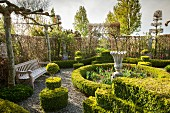 Garden bench, stone urn and beds of tulips inside circular hedge surrounded by gravel patch and clipped box bushes
