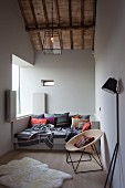 An Wand lehnende schwarze Stehleuchte und Korbstuhl vor moderner Tagesliege mit Kissen