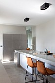 Barstools with leather shell seats at island counter with concrete worksurface in minimalist kitchen