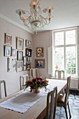 Gallery of pictures in dining room with Venetian-style glass chandelier