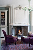 Elegant armchair and ottoman with purple upholstery in front of fireplace in grand interior