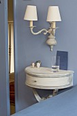 Semicircular console table below sconce lamp with lampshades on pastel-blue wall