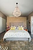 Doppelbett mit gepolstertem Kopfteil und drapierte Kissen vor Raumteiler, oberhalb Kronleuchter, in modernem Schlafzimmer