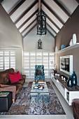 Braune und blaue Farbtöne in Loungebereich mit sichtbarem Dachstuhl, Sofa mit Samtbezug und gemusterter Sessel um gebogenem Glas Couchtisch,