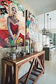 Sammlerstücke auf Wandtisch aus Holz vor Bildern an Wand aufgehängt, im Hintergrund Theke