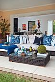 Dunkle Rattan Outdoormöbel, Bodentisch und Sofa mit gemusterten Kissen in Blau und Weiss auf gefliester Wohnterrasse
