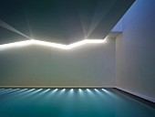 Indoor swimming pool with submerged lights and indirect ceiling lighting in angular ceiling
