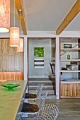 Metall-Barhocker vor Theke unter Pendelleuchten an Holzbalkendecke in offenem Wohnraum mit Treppenaufgang
