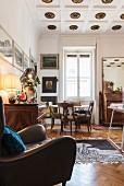 Wohnraumecke mit Stuckrosetten, braunem Ledersessel und Essplatz vor Fenster mit antiken Stühle um weißen Klassiker 'Tulip Table'