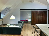 Open-plan interior with exotic-wood sliding door in minimalist designer style