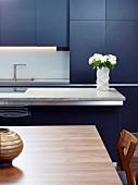Blaugraue Designerküche mit Küchentheke, indirekter Beleuchtung und Edelholztisch